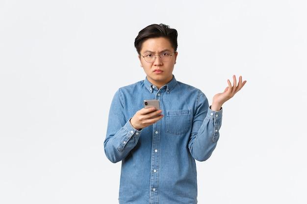 Zdezorientowany i rozczarowany azjata w okularach nie może zrozumieć powodów, stojąc na białym tle, podnosząc rękę do góry zdziwiony po zobaczeniu czegoś frustrującego w telefonie komórkowym, białe tło.