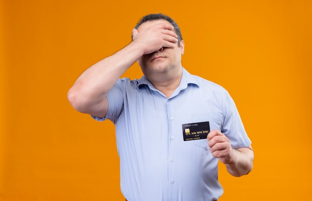 Zdezorientowany i zestresowany mężczyzna w średnim wieku w niebieskiej koszuli w paski, trzymając kartę kredytową, zasłaniając oczy ręką