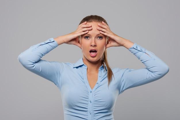 Zdezorientowany i zszokowany bizneswoman, trzymając się za ręce na głowie