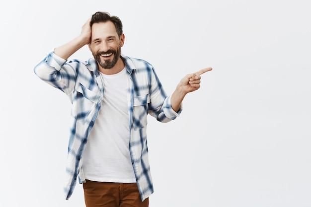 Zdezorientowany i zszokowany brodaty dojrzały mężczyzna pozowanie