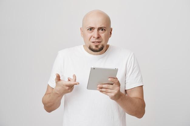 Zdezorientowany łysy mężczyzna wpatruje się zdziwiony w cyfrowy tablet