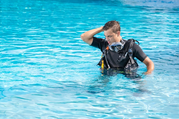 Zdezorientowany mężczyzna ćwiczy w basenie przed nurkowaniem