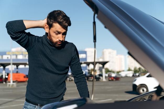 Zdezorientowany mężczyzna patrzący na maszynownię swojego samochodu wydaje się mieć nienormalny stan. facet myśli, co robić. koncepcja ubezpieczenia samochodu