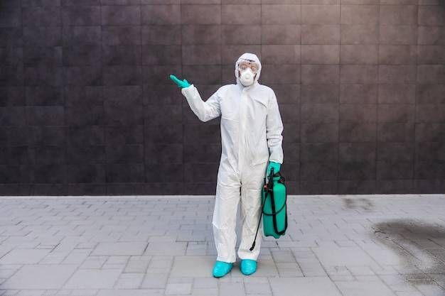 Zdezorientowany mężczyzna trzyma opryskiwacz ze środkiem dezynfekującym