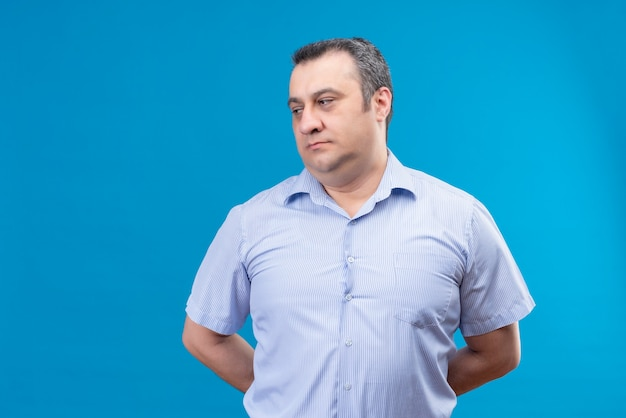 Zdezorientowany mężczyzna w średnim wieku w niebieskiej koszuli w paski myśli kładzie ręce na plecach na niebieskim polu