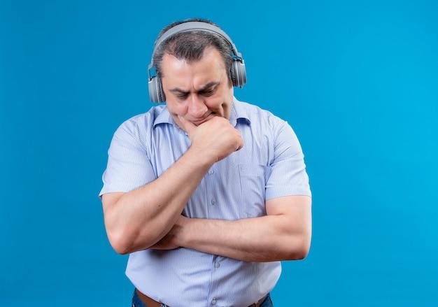 Zdezorientowany mężczyzna w średnim wieku w niebieskiej koszuli w paski położył rękę na brodzie, stojąc poważnie słuchając czegoś ze słuchawkami na niebieskim polu