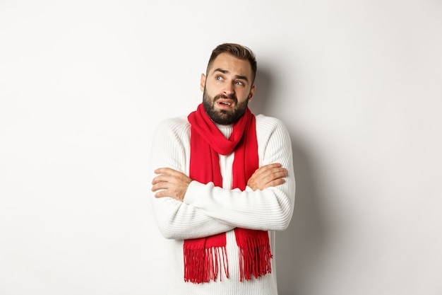 Zdezorientowany mężczyzna wyglądający z powątpiewaniem, stojący ze skrzyżowanymi rękami i czujący zimno w zimie, ubrany w świąteczny sweter z czerwonym szalikiem, stojący na białym tle.