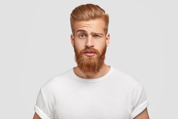 Zdezorientowany mężczyzna z gęstą rudą brodą unosi brwi
