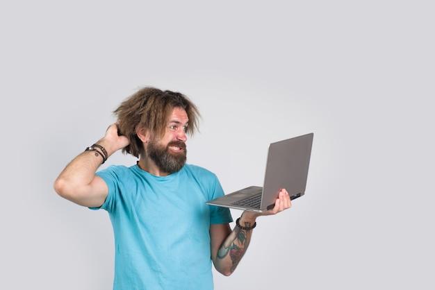 Zdezorientowany mężczyzna z laptopem brodaty mężczyzna trzyma urządzenie cyfrowe laptopa poważny brodaty mężczyzna z laptopem
