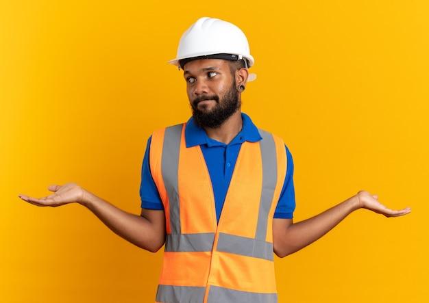 Zdezorientowany młody afro-amerykański budowniczy mężczyzna w mundurze z hełmem ochronnym, trzymając ręce otwarte, patrząc na bok na białym tle na pomarańczowym tle z kopią przestrzeni