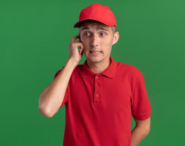Zdezorientowany młody blond chłopiec kładzie palec na skroni i patrzy na bok odizolowany na zielonej ścianie z miejscem na kopię