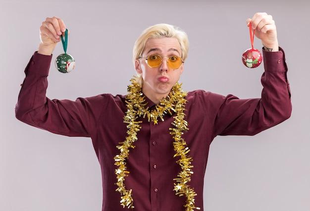 Zdezorientowany młody blondyn w okularach z blichtrową girlandą wokół szyi podnoszącą świąteczne bombki w górę patrząc na kamerę na białym tle