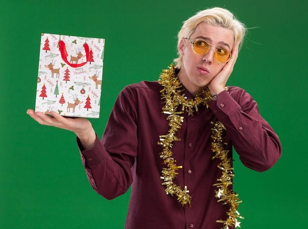 Zdezorientowany młody blondyn w okularach z świecącą girlandą na szyi trzyma torbę z prezentami świątecznymi patrząc z boku, trzymając rękę na twarzy odizolowaną na zielonej ścianie