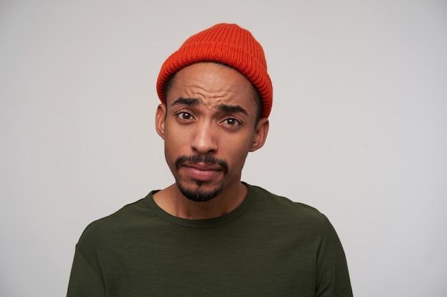 Zdezorientowany młody brązowooki ciemnoskóry mężczyzna z brodą patrzy zmieszany na kamery i ma złożone usta, ubrany w zwykły strój, pozując na białym