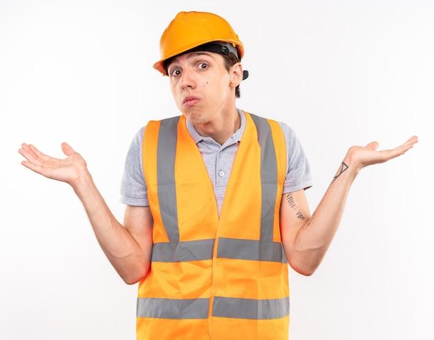Zdezorientowany młody budowniczy mężczyzna w mundurze rozłożonymi rękami na białym tle na białej ścianie