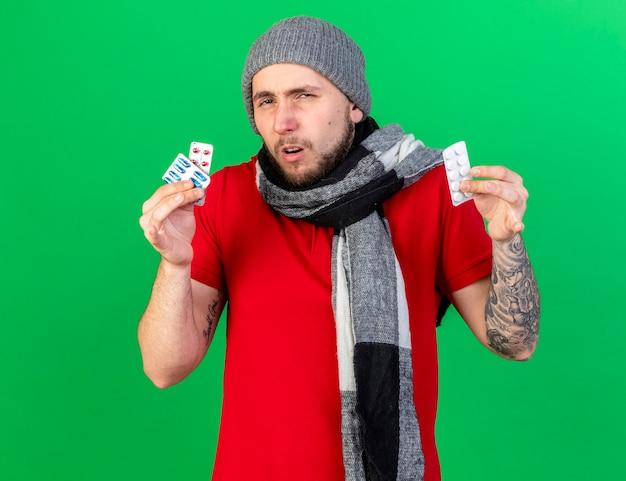 Zdezorientowany młody chory człowiek ubrany w czapkę zimową i szalik trzyma paczki pigułek medycznych na białym tle na zielonej ścianie