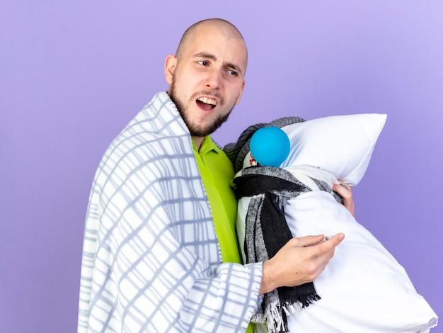 Zdezorientowany młody chory mężczyzna owinięty w kratę stoi bokiem, trzymając poduszkę z narzędziami medycznymi na fioletowej ścianie