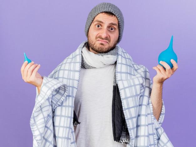 Zdezorientowany młody chory mężczyzna w czapce zimowej z szalikiem owiniętym w kratę, trzymający lewatywy i rozkładający ręce na białym tle na fioletowym tle