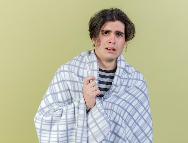 Zdezorientowany młody chory zawinięty w kratę, trzymając termometr na białym tle na oliwkowej zieleni