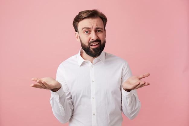 Zdezorientowany młody ciemnowłosy mężczyzna z krótką fryzurą i bujną brodą, pokazujący ręce i unoszący dziwnie brwi, wydymający wargi na różowej ścianie w oficjalnym ubraniu