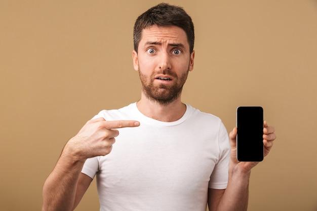 Zdezorientowany młody człowiek dorywczo pokazuje pusty ekran telefonu komórkowego na białym tle
