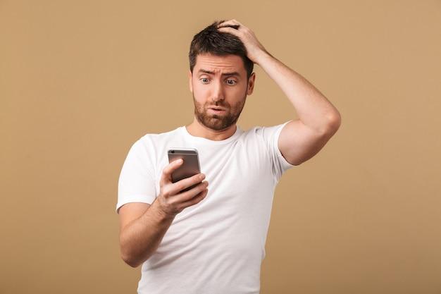 Zdezorientowany młody człowiek dorywczo trzymając telefon komórkowy na białym tle