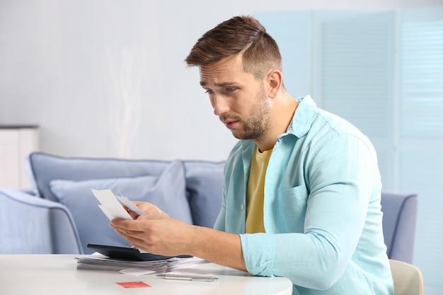 Zdezorientowany młody człowiek obliczający podatki w domu