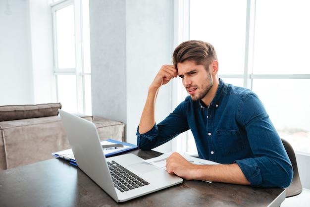 Zdezorientowany młody człowiek siedzi w pobliżu laptopa i trzymając głowę ręką. patrząc na laptopa