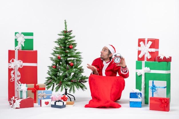 Zdezorientowany młody człowiek świętuje nowy rok lub święta bożego narodzenia siedząc na ziemi i trzymając zegar w pobliżu prezentów i dekorowanego drzewa xsmas na białym tle