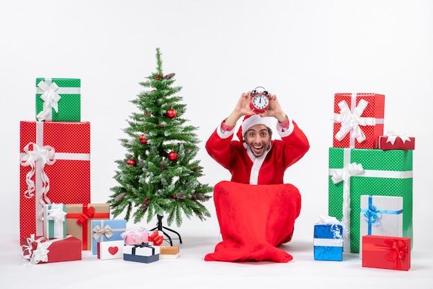 Zdezorientowany młody człowiek świętuje nowy rok lub święta bożego narodzenia siedząc na ziemi i trzymając zegar w pobliżu prezentów i udekorowane drzewo xsmas sprawdzające jej czas na białym tle