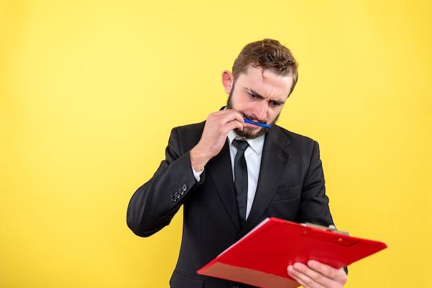 Zdezorientowany młody człowiek trzyma pióro w ustach i dokumenty w ręku