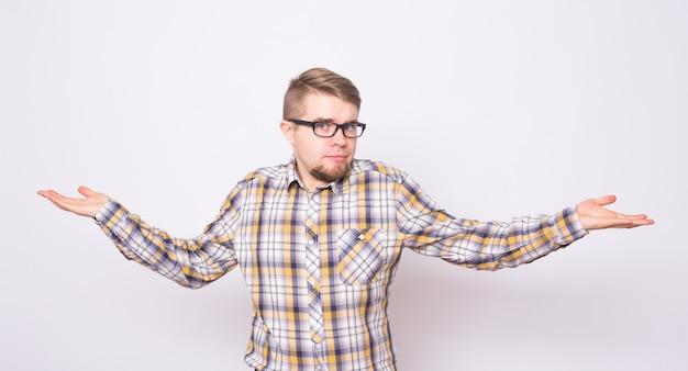 Zdezorientowany młody człowiek ubrany w koszulę stojącą na białym