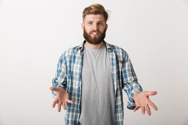 Zdezorientowany młody człowiek ubrany w kraciastą koszulę stojący na białym tle