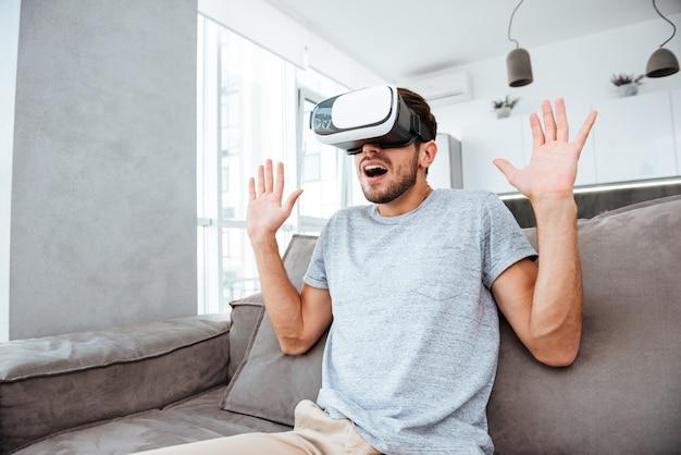 Zdezorientowany młody człowiek ubrany w urządzenie wirtualnej rzeczywistości siedząc na kanapie
