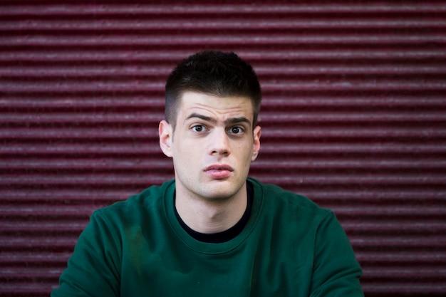 Zdezorientowany młody człowiek w zielonej koszuli