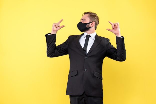 Zdezorientowany młody człowiek wskazujący palcami po obu stronach, nie będąc pewnym, który wybrać na żółto