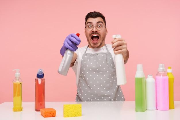 Zdezorientowany młody, dość krótkowłosy brunetka mężczyzna podnosi ręce z butelkami ze sprayem i wygląda podekscytowany z szeroko otwartymi ustami, pozując na różowo