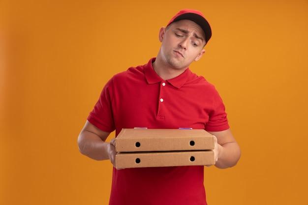Zdezorientowany młody dostawca ubrany w mundur z czapką, trzymając i patrząc na pudełka po pizzy na białym tle na pomarańczowej ścianie