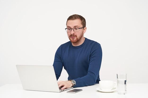 Zdezorientowany młody jasnowłosy mężczyzna w okularach trzymający ręce na klawiaturze i patrząc zaskoczony na ekran swojego laptopa, siedząc na białym tle