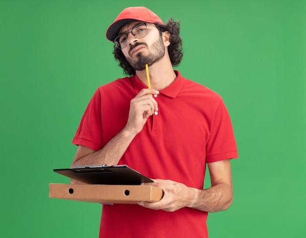Zdezorientowany młody kaukaski dostawca w czerwonym mundurze i czapce w okularach, trzymając schowek na paczkę pizzy, dotykając podbródka ołówkiem