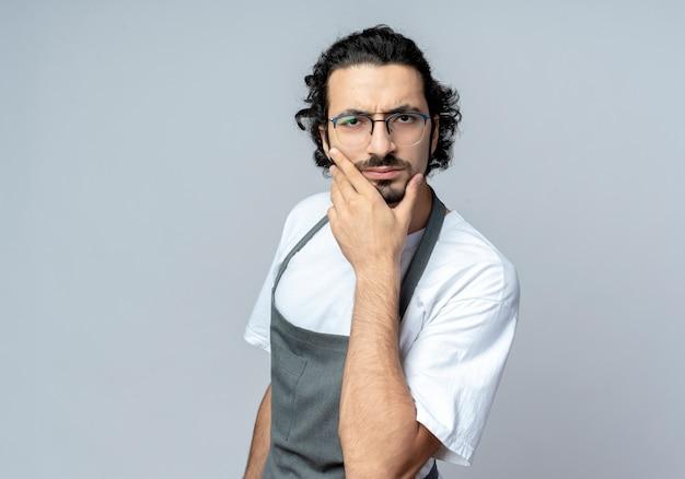 Zdezorientowany młody kaukaski fryzjer męski w okularach i falującej opasce do włosów w mundurze kładąc dłoń na brodzie na białym tle na białym tle z miejsca na kopię