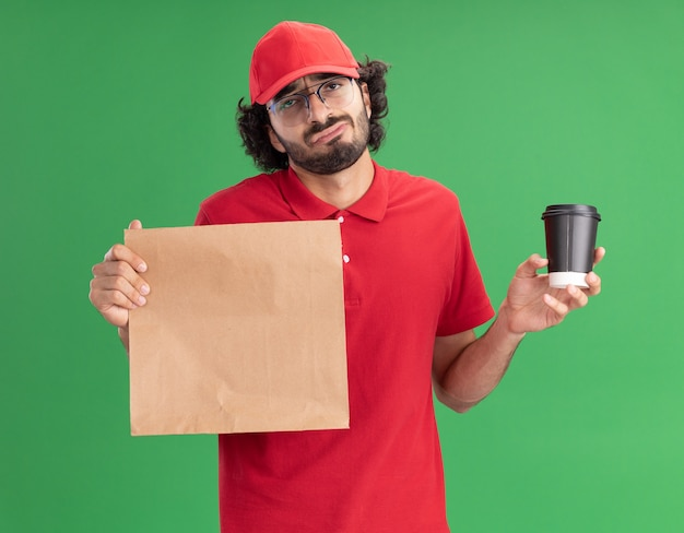 Zdezorientowany młody kaukaski mężczyzna dostawy w czerwonym mundurze i czapce w okularach trzymających papierową paczkę i plastikową filiżankę kawy na zielonej ścianie