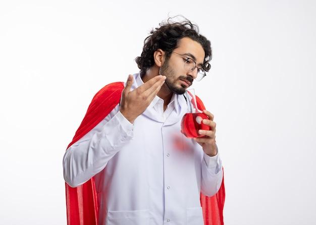 Zdezorientowany młody kaukaski mężczyzna w okularach optycznych, ubrany w mundur lekarza z czerwonym płaszczem i stetoskopem wokół szyi, trzyma i wącha czerwoną ciecz chemiczną w szklanej kolbie