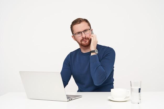 Zdezorientowany młody, ładny brodaty facet ubrany w zwykłe ubrania, rozmawiający przez telefon i marszczący brwi, patrząc zdziwiony aparat ar, odizolowany na białym tle