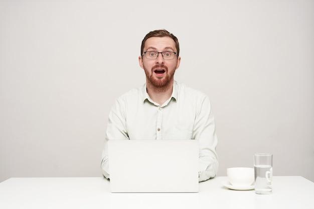 Zdezorientowany młody, ładny brodaty mężczyzna ubrany w białą koszulę, patrząc zaskoczony na aparat z szeroko otwartymi ustami podczas pisania tekstu na swoim laptopie, odizolowany na białym tle