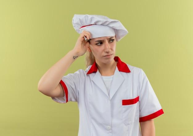Zdezorientowany młody ładny kucharz w mundurze szefa kuchni, patrząc na bok, kładąc rękę na głowie odizolowaną na zielonej ścianie