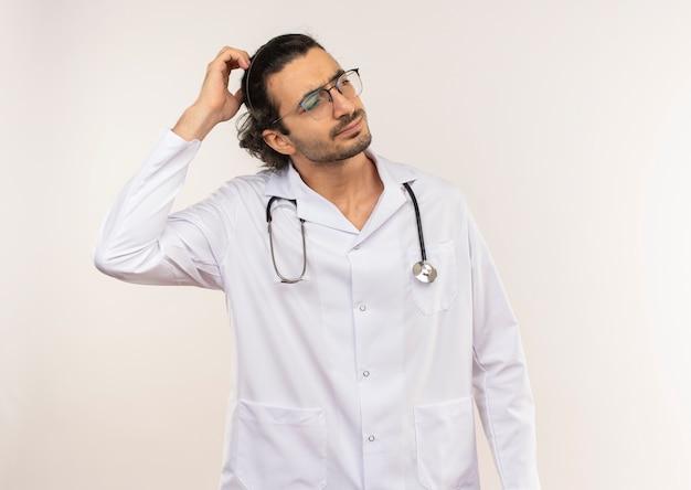 Zdezorientowany młody lekarz mężczyzna z okularami optycznymi na sobie białą szatę ze stetoskopem, kładąc rękę na głowie