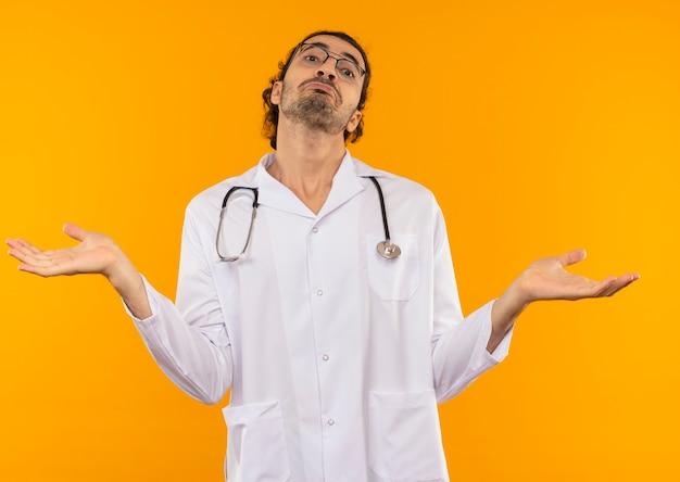 Zdezorientowany młody lekarz z okularami medycznymi w szacie medycznej ze stetoskopem rozkłada ręce