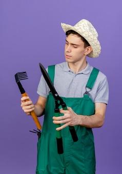 Zdezorientowany młody męski ogrodnik na sobie kapelusz ogrodniczy posiada grabie i maszynki do strzyżenia