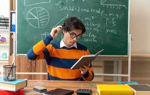 Zdezorientowany młody nauczyciel geometrii kaukaskiej w okularach, siedzący przy biurku z szkolnymi narzędziami w klasie, trzymający i patrzący na notatnik, dotykając głową piórem